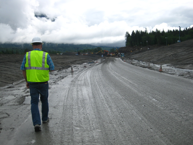 Oso, Wash., May 19, 2014 -- On Monday morning, May 19, FEMA Public Assistance Project Specialist Ronald Hepler observes the progress made clearing slide debris from State Route 530 in Oso, Washington