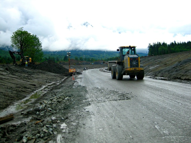 Oso, Wash., May 19, 2014 -- Workers clear State Route 530 of debris from a slide that took place March 22. Efforts are being made to reopen the highway