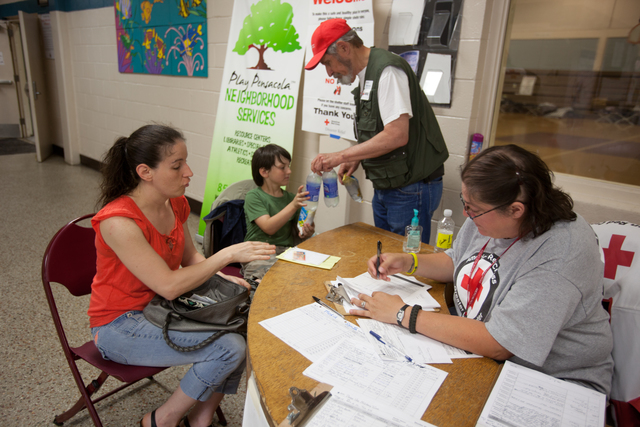 Pensacola, Fla., May 10, 2014 -- American Red Cross volunteer, Heather LaBounty checks Katerina Pendergrast and son, Zachery into a Red Cross shelter in Pensacola after flash flooding made their home unlivable. Andrea Booher/FEMA