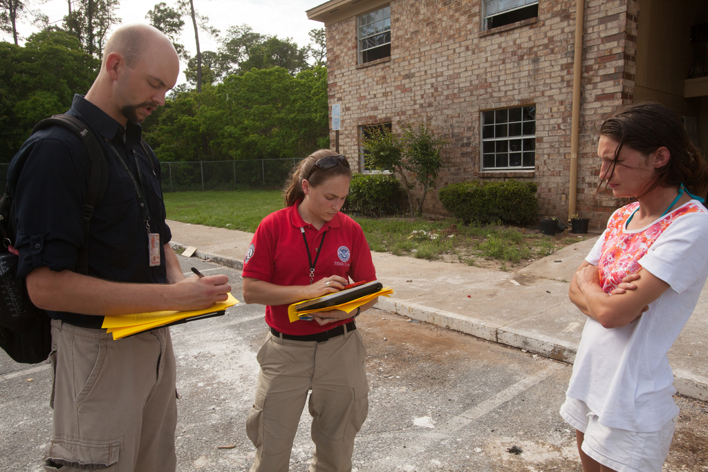 """""""Pensacola, Fla., May 12, 2014 -- FEMA's Disaster Survivor Assistance Team (DSAT) members, Collier Brown and Mike Rood check on the status of FEMA applicant, Heather Quick at her home in Pensacola. After flash flooding occurred along parts of the Florida Panhandle,  DSAT teams were deployed to go door to door and check on the welfare of  survivors. Andrea Booher/FEMA"""""""