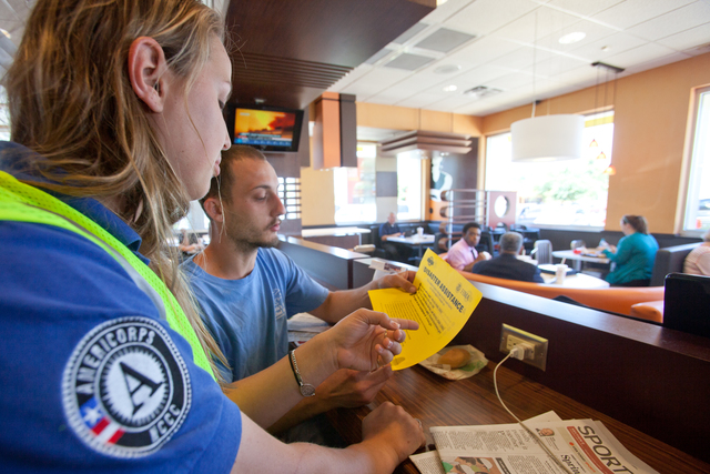 Pensacola, Fla., May 15, 2014 -- FEMA Corps member, Marie Orechoff provides disaster information to a disaster survivor in a local restaurant.  Orechoff is a member of FEMA's Disaster Survivor Assistance Team (DSAT) and was deployed to Pensacola after a flash flood occurred in the area. Andrea Booher/FEMA