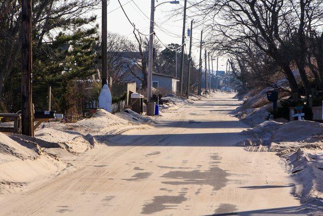 Reeds Beach, N.J., Jan. 8, 2013 -- Shortly after Hurricane Sandy some roads were impassable along this beach community because of the sand left by the storm. Two months afterward, sand is piled along side to clear roads that are still covered by sand. Steve Zumwalt/FEMA
