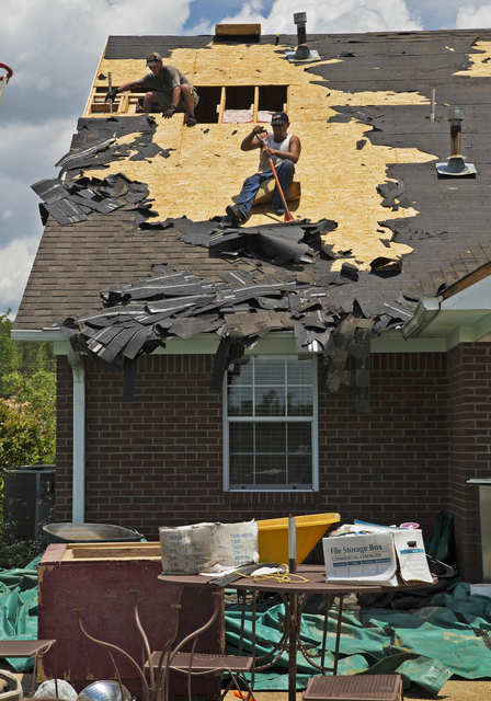Saltillo, Miss., June 12, 2014 -- Workers are removing insulation and sections of this damaged roof, while others replace roof shingles.  The home was affected by the April tornadoes that swept through Saltillo.  FEMA/Yuisa Rios