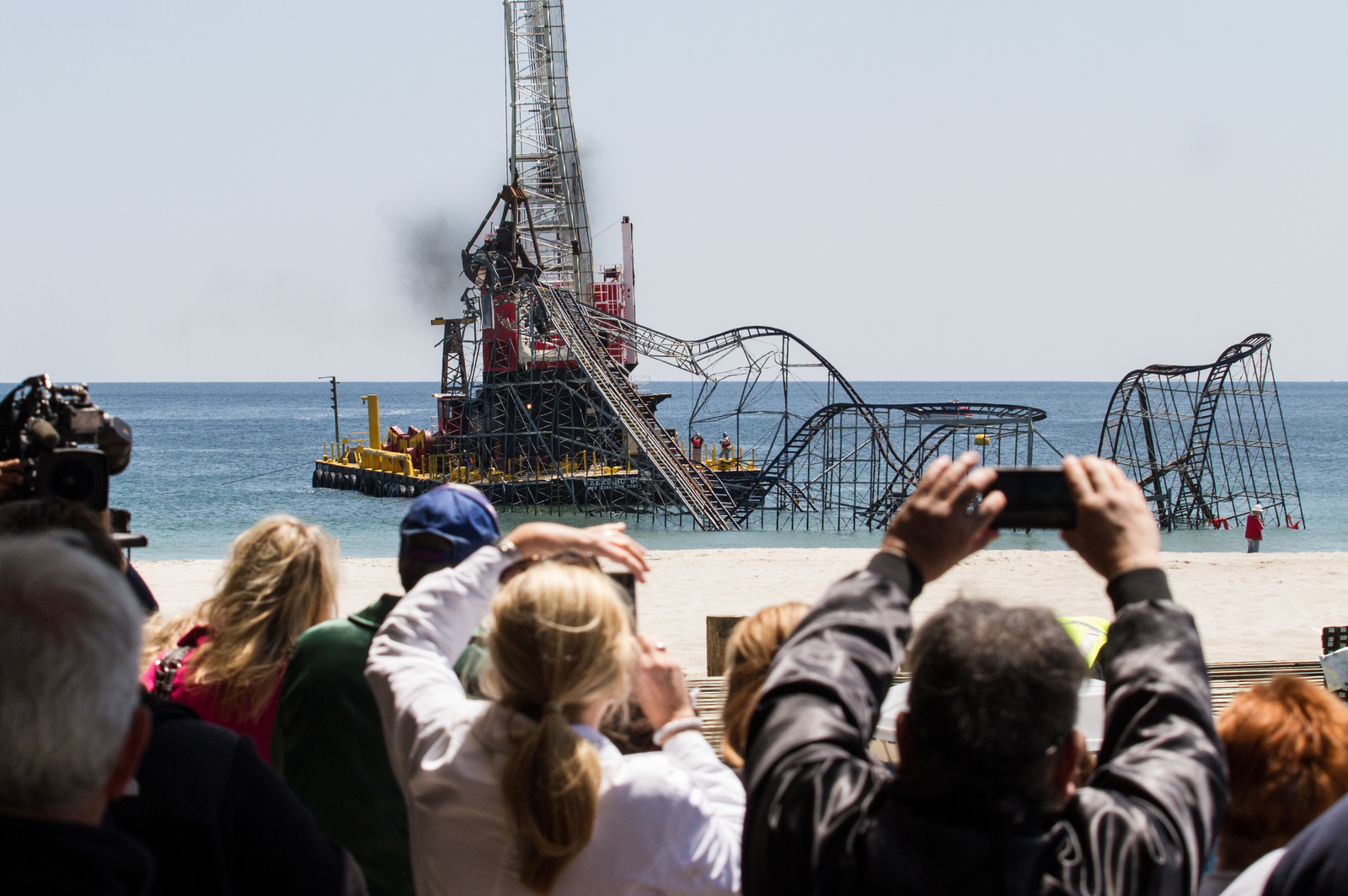 Seaside Heights, N.J., May 14, 2013 -- News media representatives and locals gather to watch the demolition of Casino Pier's Jet Star roller coaster that collapsed into the ocean during Hurricane Sandy last fall. The demolition of the roller coaster, once an iconic symbol of Sandy's fury, now becomes a symbol of recovery and new beginnings for Seaside Heights. Rosanna Arias/FEMA