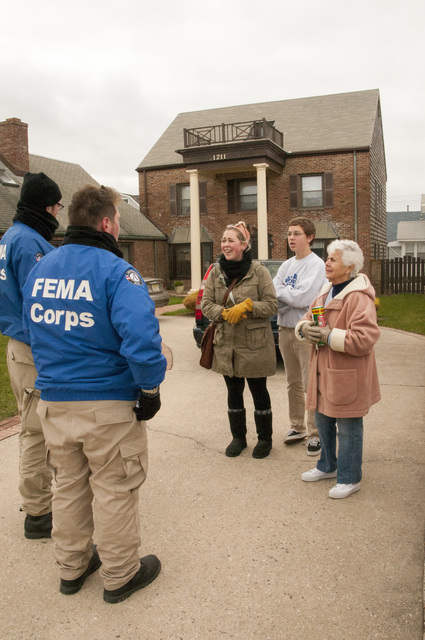 Seaside Park, N.J., Nov. 24, 2012 -- Garrett Manley and Bryan Adams (l), FEMA Corps members, talk to residents at their Seaside Park home. FEMA and FEMA Corps are sending out personnel to provide residents with information about registration and assistance where appropriate.  Photo by Patsy Lynch/FEMA