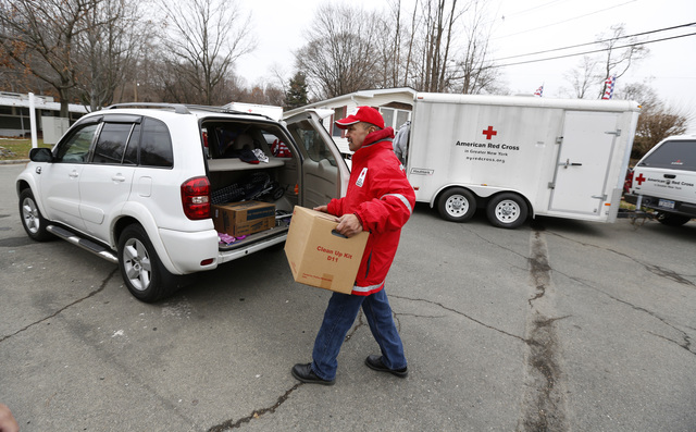 Stoney Point, N.Y., Dec. 1, 2012 -- Red Cross volunteer J.J. Finn places food in the vehicle of a survivor of Hurricane Sandy in Stoney Point, NY, December 1, 2012. FEMA is working with various partners including federal, state local and tribal governments, voluntary faith-based and community-based organizations, along with the private sector, to assist residents impacted by Hurricane Sandy. Chris Kleponis/ FEMA