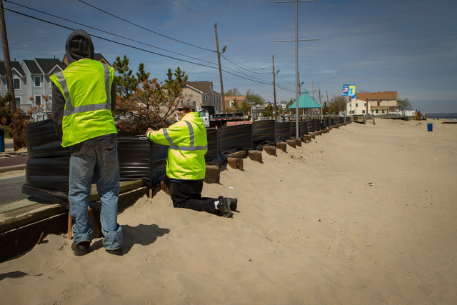 Union Beach, N.J., April 30, 2013 -- Workers from Union Beach Public Works  construct temporary barricades to prevent beach sand from blowing into the streets until a permanent solution is created by the Corps of Engineers. Rosanna Arias/FEMA