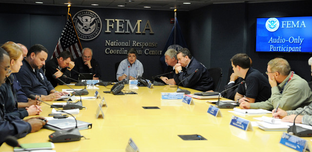 Washington, D.C., Oct. 30, 2012 -- Department of Homeland Security Secretary Janet Napolitano, center, and FEMA Administrator Craig Fugate, left, participate in a briefing at the National Response Coordination Center at FEMA headquarters on October 30, 2012. Jocelyn Augustino/FEMA Photo