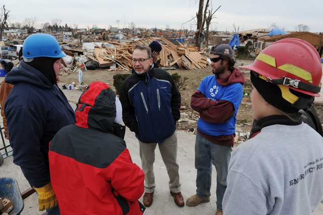 Washington, Ill., December 5, 2013 -- Rev. David Myers, right, Senior Advisor to the FEMA Administrator/Director Center of Faith-based & Neighborhood Partnerships, center, speaks with NECHAMA Jewish Response to Disaster operations manager Dan Hoeft, left,  and All Hands Volunteers director of US Disaster Response Sherry Buresh, second from left, as well as other volunteers in a neighborhood where the groups are helping with volunteer support for cleanup.  Myers met with Voluntary Organizations Active in Disaster groups to discuss responses to the disaster and discuss coordination and collaboration of partners. Jocelyn Augustino/FEMA