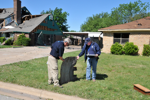 West, Texas, April 20, 2013 --Two members of the state/federal Preliminary Damage Assessment Team--Sandy Eastham and Michael Hamm--look at a piece of metal thrown into a front yard by the explosion of a fertilizer plant. FEMA/Earl Armstrong