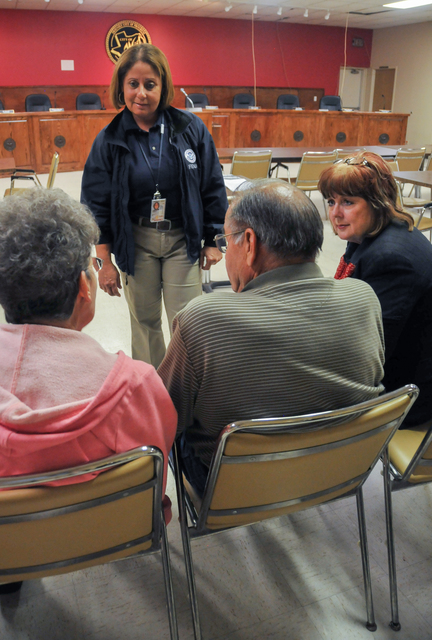West, Texas, May 20, 2013 -- Carmen Rodriguez (standing), an external affairs specialist for the Federal Emergency Management Agency, and Mary Moren-Cornelius (seated, right), manager of FEMA's Disaster Recovery Center, tell survivors of the fertilizer plant explosion about the disaster assistance available to them. FEMA is helping residents recover from the disaster. Norman Lenburg/FEMA