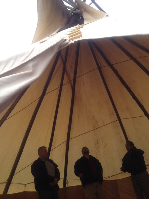 Window Rock, Ariz., March 20, 2013 -- From inside a Native American Tipi, Mike Salabiye, Planner for the Navajo Nation Department of Behavioral Health Services, explains the intricate design structure of the Tipi to Sam Ronveaux, FEMA Region IX Infrastructure Branch Director and Bruce Knabenshue, the FEMA Public Assistance Task Force Leader for FEMA-4104-DR. The Tipi shown here was used in one of several religious or traditional ceremonies during the Navajo Nation Prayer Day celebrated March 18 - 19, 2013. Photo by Rose Whitehair/Navajo Nation Emergency Manager