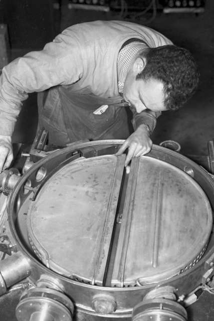 Franz N. D. Kurie working on dees (D's) of 27-inch cyclotron tank #3. [Photographer: Donald Cooksey]