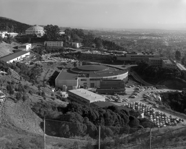 General view of 184-inch cyclotron with Bevatron in foreground. Stack parking visible in lower right. Photograph taken February 24, 1960. Building-2677