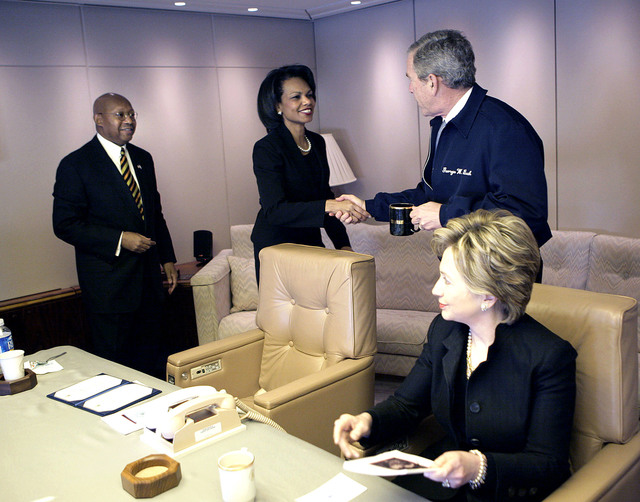 Guests aboard Air Force One. Flight to Georgia for the funeral of Coretta Scott King. The President greets Secretary of State Condoleezza Rice. HUD Secretary Alphonso Jackson and New York Senator Hillary Rodham Clinton are present.