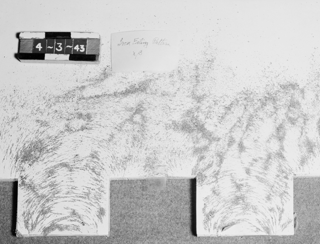 Iron filing shot (showing X-Beta pattern), residual fluid only. Associated with Wilson Marcy Powell, Professor of Physics, UC Berkeley, Lawrence Berkeley Laboratory, Lawrence Livermore Laboratory, and Oak Ridge National Laboratory; Guggenheim Fellowship, Manhattan Project, 184-inch cyclotron, head of magnet group. Formerly confidential. Photograph taken April 3, 1943. Magnet-27
