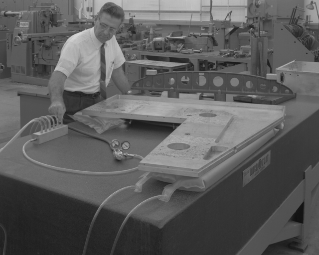 Jack Kroll with the base plate for the 80-inch stereo camera. Polyethylene bags to keep part from sagging while being scraped to 0.0005-inch. Photograph taken June 8, 1965. Bubble Chamber-1479 -  Photographer: George Kagawa