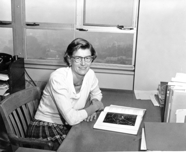 Portrait of physicist Dr. Marian Whitehead sitting at her desk. Her research is in strange-particle physics, using emulsion, counter and bubble chamber techniques. Morgue 1959-36 (P-1) [Photographer: Donald Cooksey]