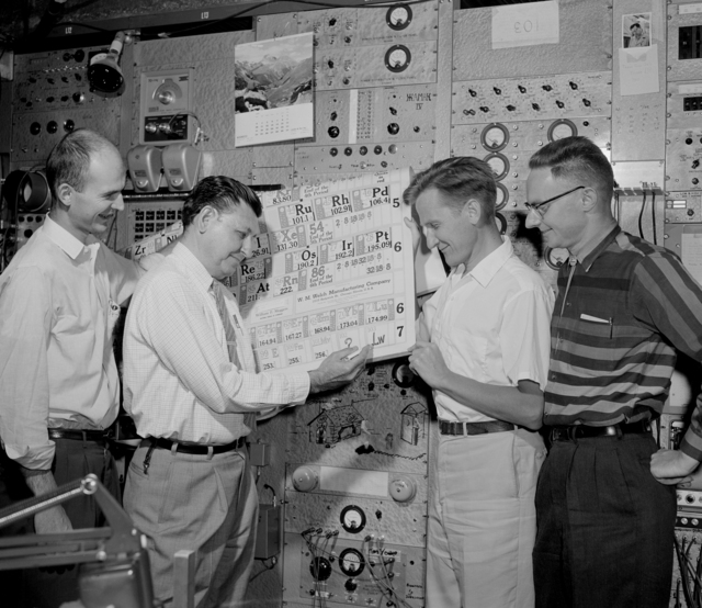 """Updating the periodic table, Albert Ghiorso adds """"Lw"""" in space 103; with codiscoverers Robert Latimer, Dr. Torbjorn Sikkeland, and Almon Larsh looking on. Morgue 1961-52 (P-1) [Photographer: Donald Cooksey]"""