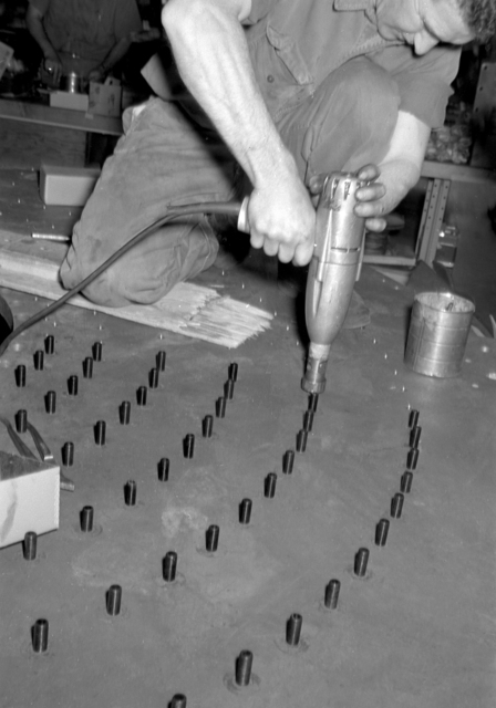 Workman cleaning out holes and placing coil hold-down bolts. Photograph taken April 2, 1957. Bubble Chamber-221