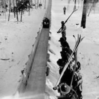 Photograph of a Group of Skiers Watching a Toboggan Coming Down the Slide