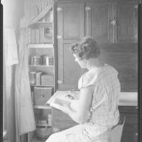 Photograph of a Farm Woman Checking Pantry Supplies