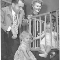 Richard and Pat Nixon observe their two young daughters. Julie Nixon sits in a crib