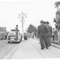 Richard Nixon campaigns to a group of people on a street corner in Arvin, California