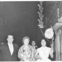 Richard Nixon holds a paper lantern on a stick during street festivities in Lisbon, Portugal.  Pat Nixon and an unidentified woman stand by his side