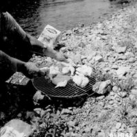 Photograph of Ranger Douglas Engleson Preparing Chicken for a Picnic Lunch