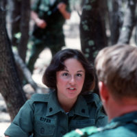A U S  Army military policewoman acts as an interrogator at a
