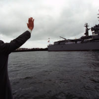 Photograph of President William J. Clinton Waving to Naval Personnel on a Nearby Naval Ship in Oakland, California
