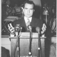 Richard Nixon stands behind a podium at the Pomona Ebell Club clubhouse during his Senatorial campaign