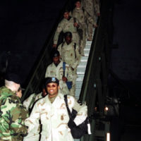 Night scene, medium shot, front view, a twelve member Security Force team coming down passenger stairs, from C-5 second deck, redeployment from Ali al Salem Air Base, Kuwait. Dover Air Force Base, Delaware, 22 February 2000