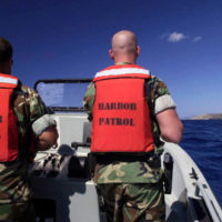 """US Navy (USN) Builder Third Class (BU3) Joe Cochan (left) and USN MASTER-at-Arms First Class (MA1) Surface Warfare (SW), Eric Fernelius, assigned to Harbor Patrol Unit Two (HP-2) man a Rigid Hull Inflatable Boat (RHIB), during a daily patrol of the Guantanamo River. From the US Navy (USN) """"ALL HANDS"""" Magazine, August 2001 Issue"""