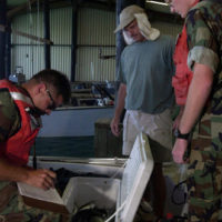 """US Navy (USN) Electronics Technician First Class (ET1) Surface Warfare (SW) Eric Fernelius (left) and USN CHIEF Torpedomans Mate Second Class (CTM2) Chris Lewis (right), assigned to Harbor Patrol Unit Two (HP-2), check the contents of a fishermans cooler inside the boathouse, while conduction Game Warden operations at Naval Station Guantanamo Bay, Cuba. From the US Navy (USN) """"ALL HANDS"""" Magazine, August 2001 Issue"""
