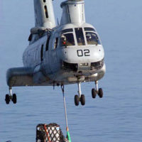 A CH-46 Sea Knight helicopter picks up pallets of supplies from the stern of the Combat Store Ship USNS NIAGARA FALLS (T-AFS 3) for delivery to the nearby aircraft carrier USS KITTY HAWK (CV 63) [Not shown] during a underway replenishment (UNREP) at sea