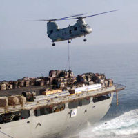 A CH-46 Sea Knight helicopter picks up pallets with supplies on them from the stern of the Combat Store Ship USNS NIAGARA FALLS (T-AFS 3) for transport over to the aircraft carrier USS KITTY HAWK (CV 63) [Not shown] during an underway replenishment (UNREP) at sea