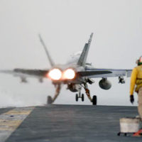 "A Flight Deck Officer, ""a shooter,"" Air Department V1 Division, watches as an F/A-18 Hornet from Fighter Attack Squadron (VFA) 192 ""Golden Dragons,"" part of Carrier Air Wing (CVW) 5, begins to clear the USS KITTY HAWK (CV 63) flightdeck. CVW 5 and KITTY HAWK are conducting flight operations in support of Operation ENDURING FREEDOM"