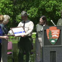 Presentation of certificate, designating the Baltimore and Annapolis Trail as a national recreation trail, to Anne Arundel County, Maryland Department of Recreation and Parks Superintendent David Dionne, center, during event at Chesapeake and Ohio Canal National Historical Park in Washington, D.C. area