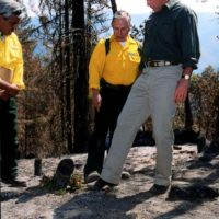 President George Bush visiting the site of the Squire Peak forest fire, Ruch, oregon, for surveys of the damage, discussions with Bureau of Land Management, state, and local officials and firefighters, and policy announcements. Photograph was selected for use in Interior video on Secretary Gale Norton era