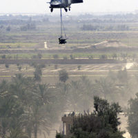 A US Army (USA) UH-60 Black Hawk helicopter is used to removes a destroyed Iraqi anti-aircraft gun from the rooftop of a building near Baghdad International Airport, during Operation IRAQI FREEDOM