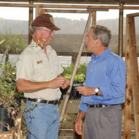 President George Bush, right, with Ralph Waycott, volunteer coordinator for the Rancho Sierra Vista Nursery, during Presidential visit to the Santa Monica Mountains National Recreation Area, Thousand Oaks, California. Visit highlighted the federal budget commitment to National Park system maintenance